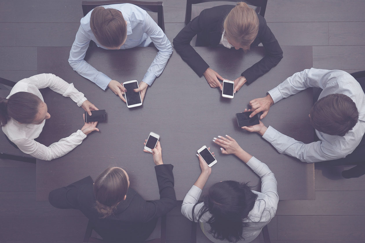 A table of business owners with phones trying to explain It management in Australia